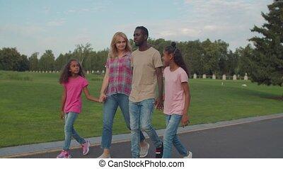 Joyful diverse family with kids relaxing in park - Joyful ...