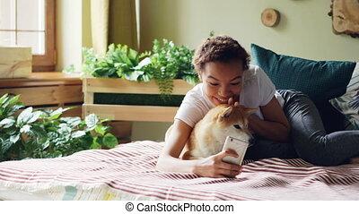 Joyful dog owner is taking selfie with cute pet lying on bed...