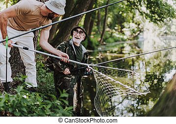 Joyful elderly fisherman enjoying weekend with his son