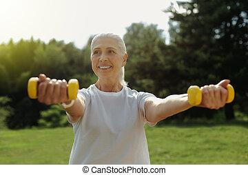 Joyful elderly lady beaming while lifting dumbbells
