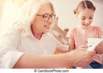 Joyful elderly lady embroidering with granddaughter