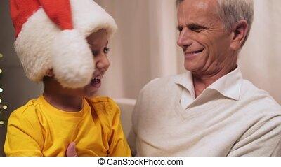 Joyful elderly man having fun with his grandson - Positive...