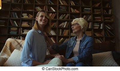 Joyful elderly woman and her daughter talking ta home -...