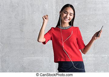 Joyful elegant girl is enjoying rhythmic song - Feel the...