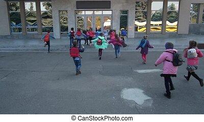 Joyful elementary age kids running to school doors - Rear ...