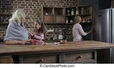 Attractive mother taking homemade cookies from the fridge and giving her happy daughter and grandmother in modern domestic kitchen. Overjoyed little girl and smiling grandmom awaiting to taste fresh handmade cookies at home. Dolly shot. Slow motion.