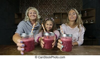 Joyful family drinking fresh berry smoothie - Portrait of...
