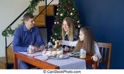 Joyful family eating christmas cookies at xmas eve -...