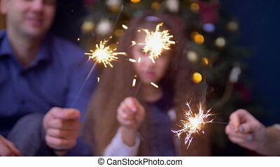Joyful family holding bengal lights at christmas - Blurry...