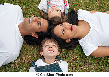 Joyful family lying in a circle on the grass