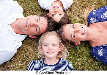 Joyful family lying in circle on the grass