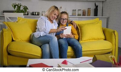 Joyful family on sofa relaxing with tablet pc
