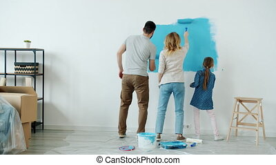 Joyful family mum dad and kid are painting wall and having fun singing and dancing during house renovation. Leisure activities and lifestyle concept.