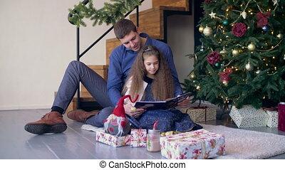 Joyful family reading fairy tale at christmas time - Loving...