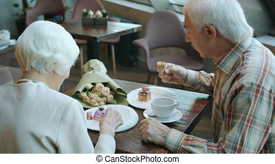 Joyful family senior man and woman are eating cakes drinking tea and enjoying conversation in restaurant. Eating out and elderly people lifestyle concept.