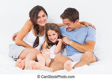 Joyful family sitting on the bed