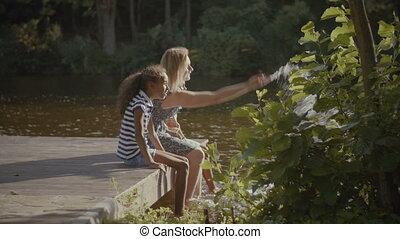 Joyful family splashing in the lake in summer