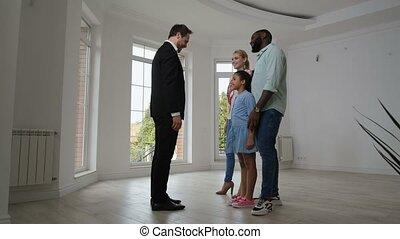 Joyful family taking keys from broker buying house