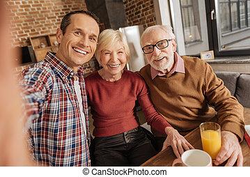 Joyful family taking selfies in the kitchen