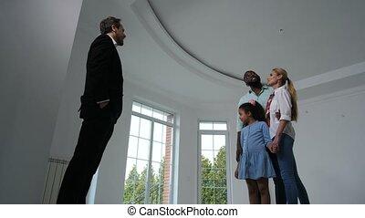 Joyful family talking to broker showing new house