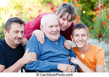 Loving family visiting grandfather at the nursing home.