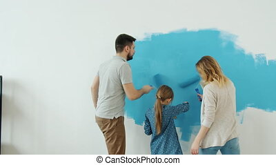 Joyful family with kid remodelling house painting wall and dancing enjoying music together. Happy young people and interior decoration concept.