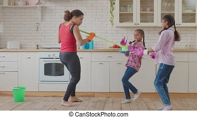 Joyful family with kids having fun during cleaning - ...