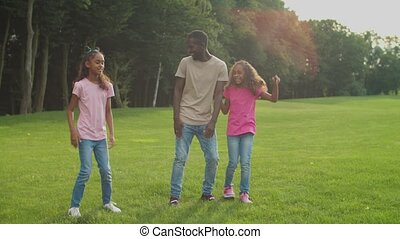 Joyful father and daughters dancing on park lawn - Carefree ...