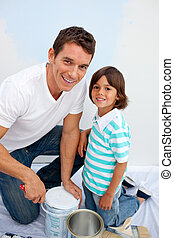 Joyful father and his son painting a room