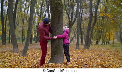 Joyful father and kid playing hide and seek in autumn -...