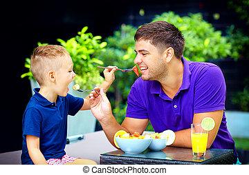 joyful father and son feeding each other with tasty fruit salad