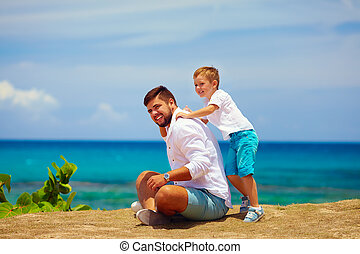 joyful father and son having fun during summer vacation