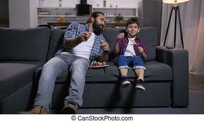 Joyful father and son viewing comedy show on tv - Joyful...