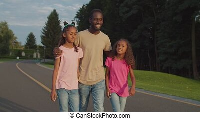 Joyful father and two daughters relaxing in park - Joyful ...