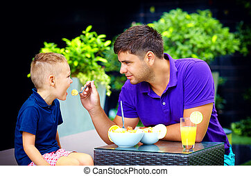 joyful father feeding son with tasty fruit salad