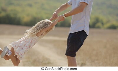 Joyful father holding his daughter's hands and turns her
