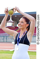 Joyful female athlete holding a trophee and a medal