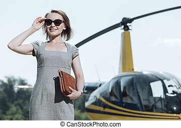 Joyful female CEO being ready for a helicopter ride