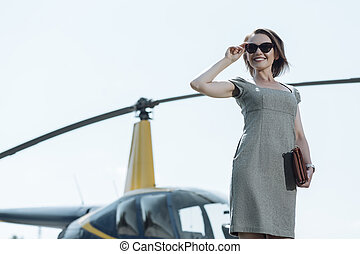 Joyful female executive being ready for helicopter ride