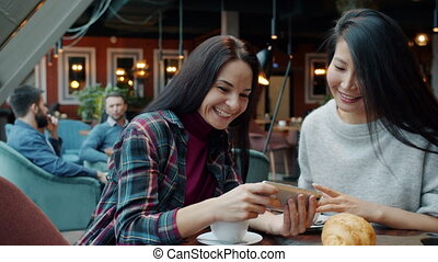Joyful female friends looking at smartphone screen in cafe talking laughing having fun