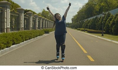 Joyful female rollerskating at speed on park path - Happy...