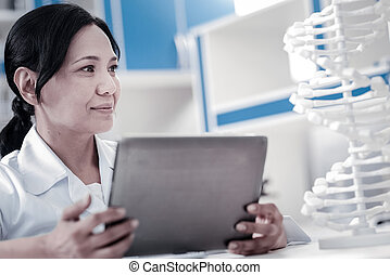 Joyful female scientist examining three dimensional model of...