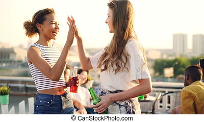 Joyful female students are talking, doing high-five, clinking bottles and drinking during rooftop party with friends. Conversation, drinks and fun concept.