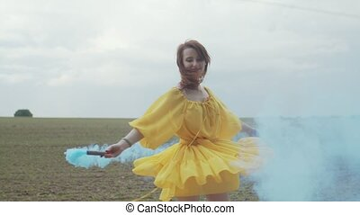 Joyful female whirling in colored smoke outdoors - Close-up...