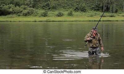 Joyful fisherman is fishing in calm river water near the...
