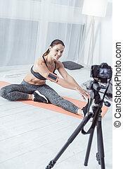Joyful fit young woman showing her flexibility