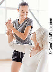 Joyful fitness coach looking at the elderly woman