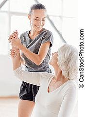 Joyful fitness coach looking at the elderly woman