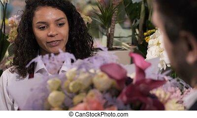 Joyful florist giving flower composition to client - Closeup...