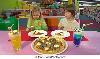 Joyful friends eating chocolate pizza during supper at ...